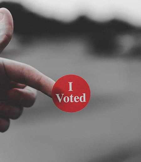 Hand holding a red sticker that says I Voted