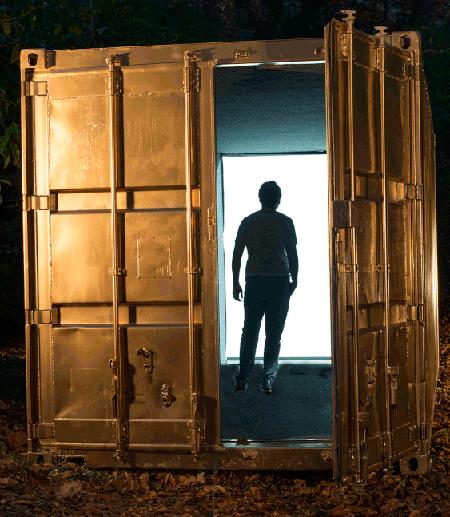 Student standing in doorway of cargo container