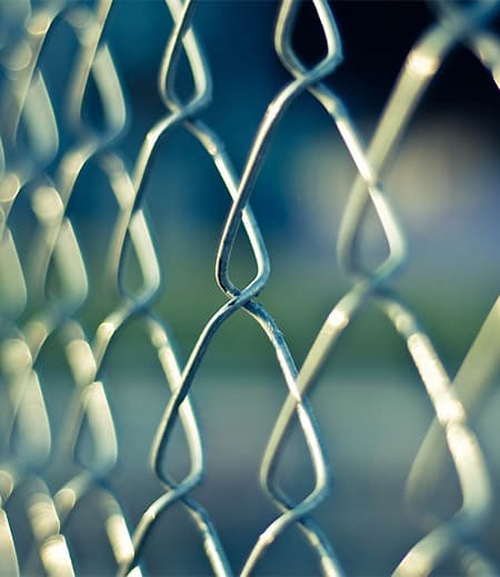 A chainlink fence on a blue background