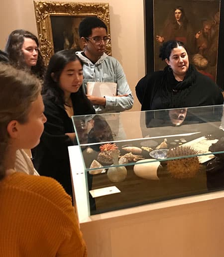 Students at Johnson Museum standing around a display of artifacts