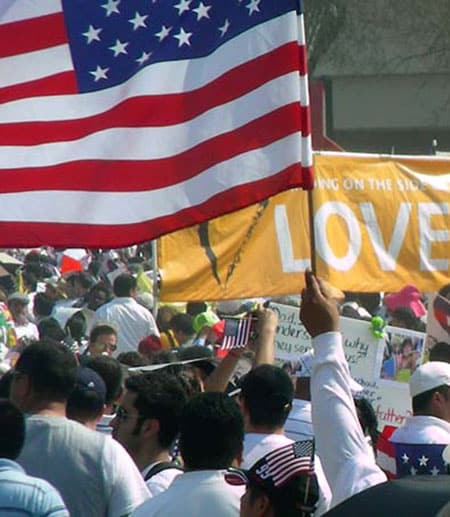 "Image of a rally with an American flag and a sign saying ""love"""