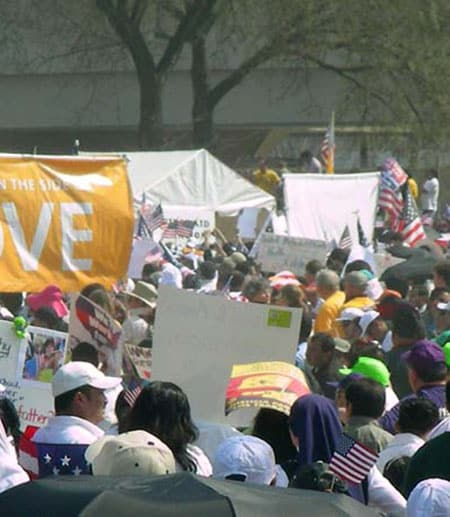 People at a rally holding American flags and signs