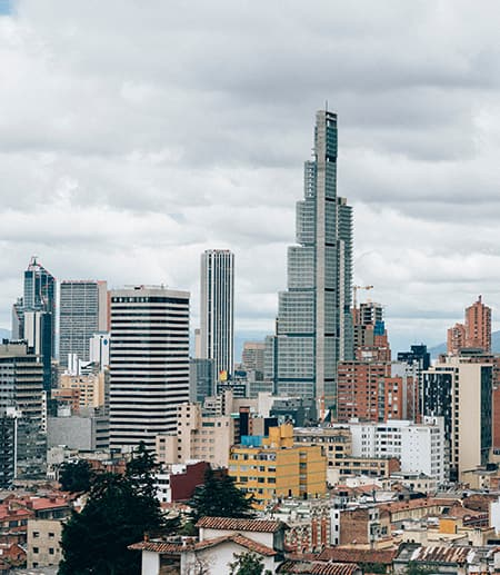 Tall silver buildings rise out of a sprawling city with mountains in the background
