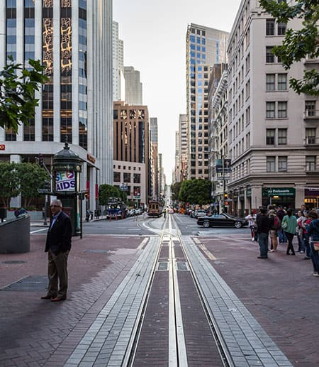 Street scene in San Francisco; tall buildings and cable car track
