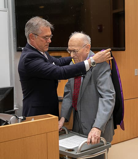 Vincent Boudreau Ph.D. '91, president of CCNY, putting the hood on Harold Scheraga for the degree Doctor of Science honoris causa,