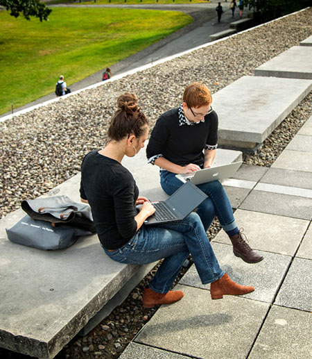 A man and woman sitting on the terrace of Olin Library, working on their computers