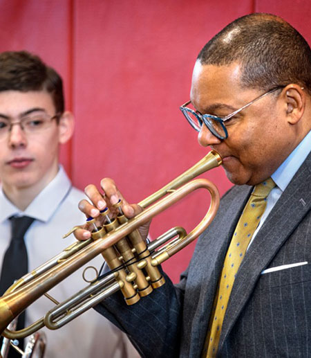 Wynton Marsalis showing a middle school student how to blow a trumpet