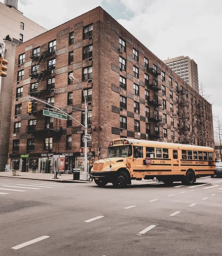 Big brick building in New York City with school bus in front of it