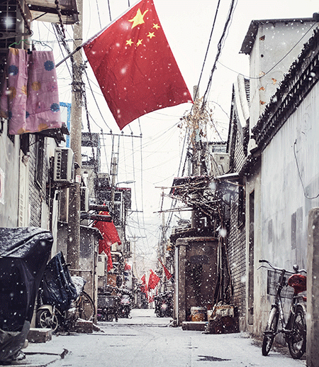 Narrow street with a red Chinese flag hanging
