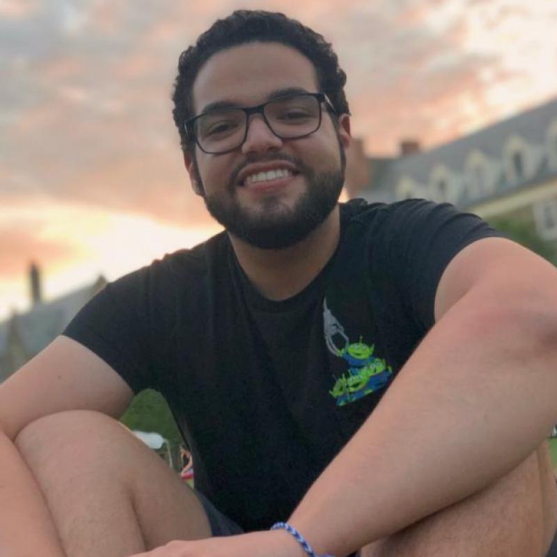 Gabriel Vergara '21 sitting on a grassy lawn.