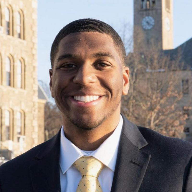 Laurence Minter '21 in a suit and tie, in front of a clocktower.