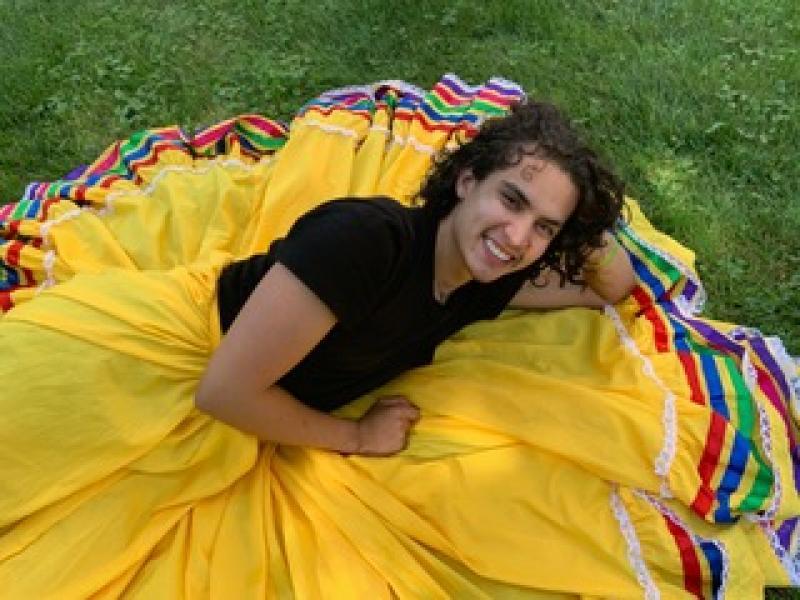 Marco Antonio Peralta-Ochoa '21 wearing a yellow skirt with ribbon trimmings.