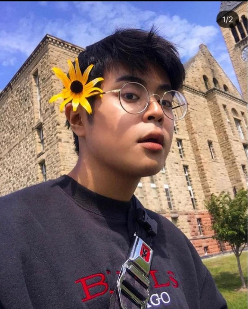 Student with a yellow flower on his head standing in front of a building
