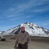 Fred Young '64, M.Eng. '66, MBA '66 in front of the summit of Cerro Chajnantor in the Atacama Desert of northern Chile, site for the Fred Young Submillimeter Telescope.
