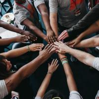 People placing their hands together in a circle
