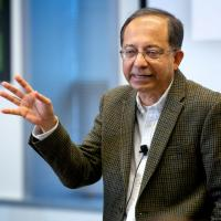 Kaushik Basu wearing a tweed jacket with hand upraised as he delivers a talk.