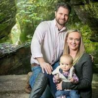 husband, wife and baby in a park