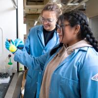 Two students wearing lab coats examining a beaker of something yellow in a lab.