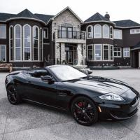 Maserati in front of elaborate house with fountain and sculpture in courtyard