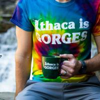 a person wearing an Ithaca is Gorges tshirt with mug and water bottle