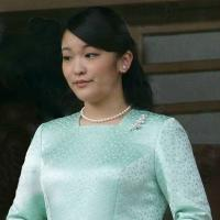 Princess Mako wearing pearl earrings, necklace and pin, and a long sleeved green dress; she is holding white gloves and a fan.