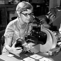 woman looking into microscope