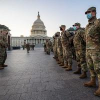 Line of soldiers in fatigues; US Capitol in background