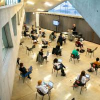 Students, sitting far apart, meet for class in Milstein Hall