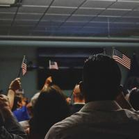People holding small American flags in a classroom