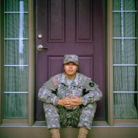 Person wearing fatigues sitting on a porch