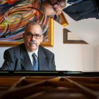Roberto Sierra, sitting at a piano