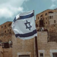 White and blue Israeli flag in front of stone buildings