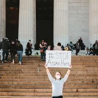 Person holding protest sign on steps