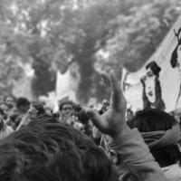 Black and white image of a rally; people around a flag