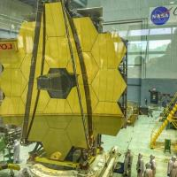 Enormous structure made of yellow hexagons; tiny people in clean suits