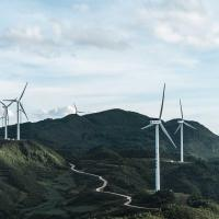 Wind turbines in a green, hilly landscape