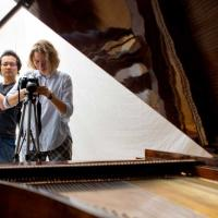 two people taking photos of a piano