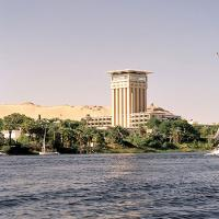 The Nile River passing a hotel, palm trees and a sandy hill