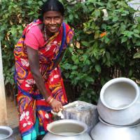 Woman in India cleaning out her water containers