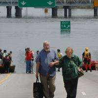 An older man and woman carrying luggage walk away from boats pulled to the edge of a flooded highway in New Orleans