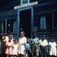 "African American children standing in front of the ""Fernwood Colored School"""