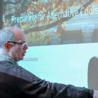 """Robert Vanderlan pointing at a screen that says """"Preparing for online instruction"""""""