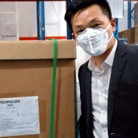 Person in mask by shipping crate