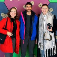 Three students holding camaras, colorful background