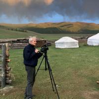 Person with camera in a field, dark sky