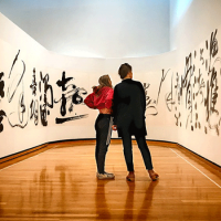 Two people surrounded by a work of art