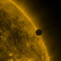 Small black sphere in front of a fiery large sphere