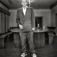 A fraternity brother in a suit standing in the living room. Credit/Copyright: Andrew Moisey