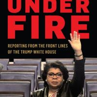 """Cover of """"Under Fire"""" book, with April Ryan holding her arm up to ask a question"""