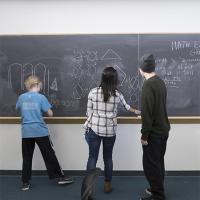 High school kids work at a chalkboard
